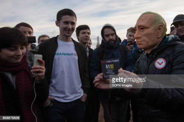 An opposition supporter seen wearing a rubber mask depicting Russian President Vladimir Putin in an unauthorized rally The President of Russia...
