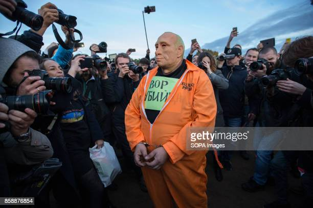 An opposition supporter seen wearing a rubber mask depicting Russian President Vladimir Putin as a prisoner while participating in an unauthorized...