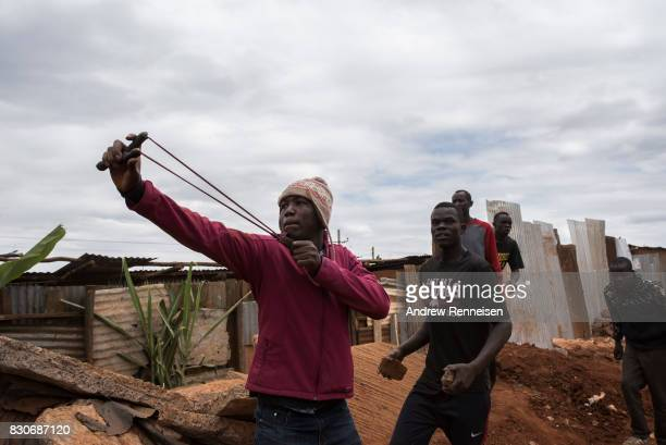 An opposition supporter shoots a slingshot at Kenyan police forces as the two sides clashed in the Kibera slum on August 12 2017 in Nairobi Kenya...