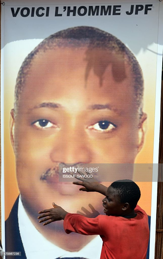 An opposition supporter stands in front of a poster depicting Togo's opposition leader and Alliance for National change candidate for Togo's presidential election, <a gi-track='captionPersonalityLinkClicked' href=/galleries/search?phrase=Jean-Pierre+Fabre&family=editorial&specificpeople=2329955 ng-click='$event.stopPropagation()'>Jean-Pierre Fabre</a>, during a presidential campaign meeting on April 21, 2015 in village of Anfoin, some 55 km east from Lome. Togo votes for a new president on April 25, with main opposition leader <a gi-track='captionPersonalityLinkClicked' href=/galleries/search?phrase=Jean-Pierre+Fabre&family=editorial&specificpeople=2329955 ng-click='$event.stopPropagation()'>Jean-Pierre Fabre</a> seeking to end nearly 50 years of rule by the Gnassingbe family.