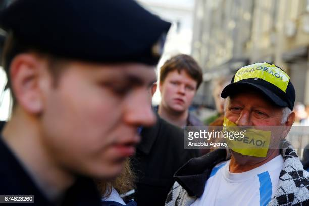 An opposition supporter wearing tape on his mouth waits in queue outside the president's administrative office to hand in his petition against...