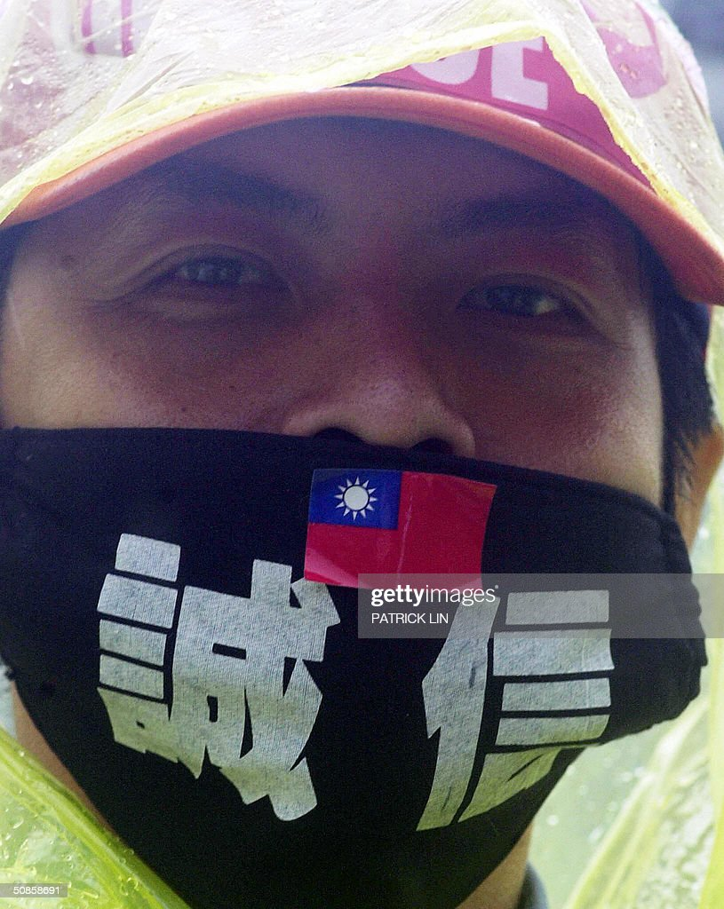 An opposition supporter wears a protest mask reading 'honesty, credit' during a protest rally at Taipei on 20 May 2004 as Chen was sworn in as the president for the second four-year term. The opposition is disputing Chen's re-election claiming it was the result of unfair election. Chen won the 20 March presidential polls by a razor-thin margin of 0.22 percent, or 30,000 votes.
