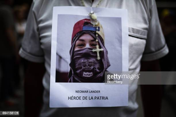 An opposition supporter wears an image of Neomar Lander with a rosary bead during a vigil in honor of the 17 yearold protester who died during a...