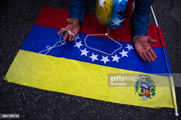 An opposition supporters kneels before a Venezuelan flag while praying with rosary beads during a vigil in honor of 17yearold protester Neomar Lander...