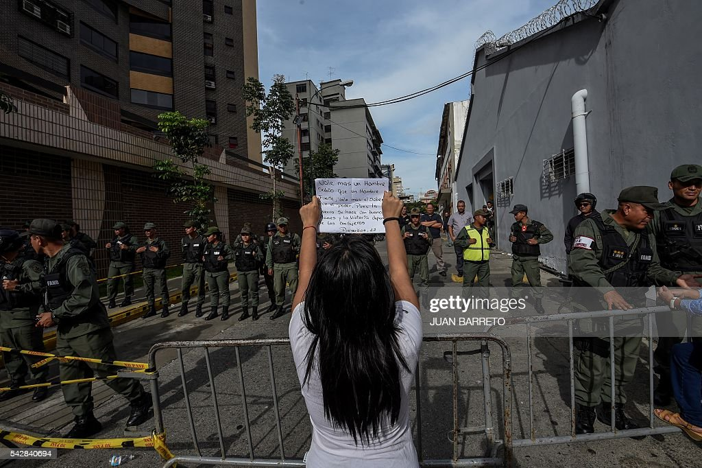 An oppositor of Venezuelan president Nicolas Maduro shows a handmade sing in front of members of national policemen during a spontaneous demonstration after the closure of centres to authenticate their signatures for a recall referendum before the National Electoral Council (CNE) in Caracas, on June 24, 2016. Soaring crime, runaway inflation and a sharply contracting economy, worsened by falling oil prices, have fueled a drive for a recall referendum to remove Maduro, as a way out of the crisis. / AFP / Juan BARRETO