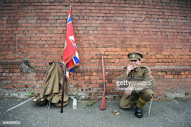 An Orange bandsman dressed in military clothes rolls a cigarette before he takes part in the annual Orange march on July 12 2016 in Belfast Northern...