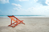 An orange beach chair rests on the white sand of the beach and Bright blue sea with white clouds, at Rayong Thailand.