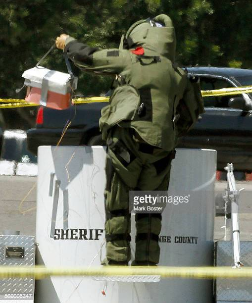 An Orange County Sheriff Bomb Squad member lowers a cache of explosives into a containment unit that were discovered in a backpack in a culvert near...