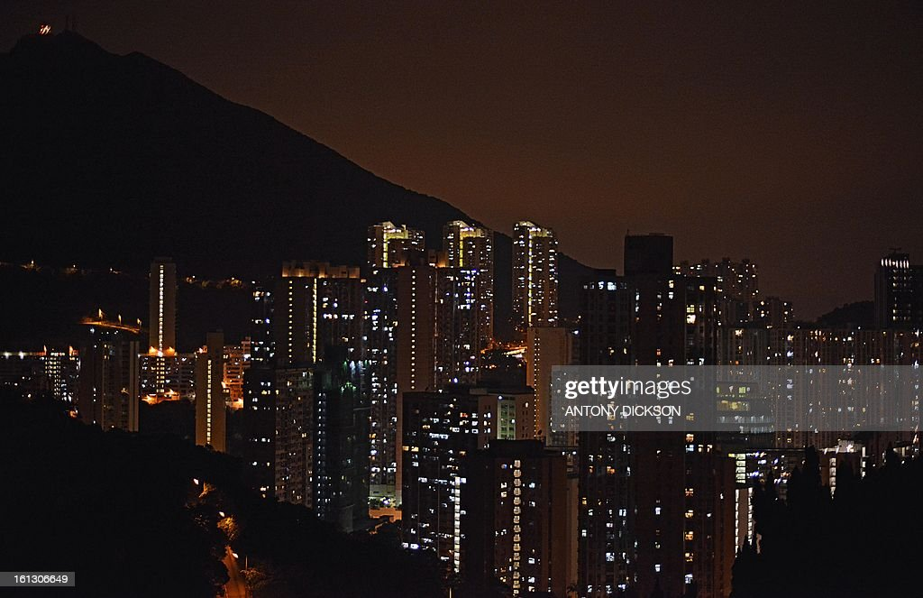 An orange sky caused by the ambient lights form the city rises above residential flats, two hours after midnight in Hong Kong on February 10, 2013. After recent scares with extremely high rates of pollution over parts of China, in a great part due to the burning of coal to produce electricity, hope may be around the corner with the development of far more environmentally friendly and effective ways to both produce electricity and in the efficiency in the way in which modern electrical appliances use electricity, such as solar and wind powered generators, and modern LED lights used for lighting and in many devices. LED's are far more efficient and in recent years have become far more competive price wise. AFP PHOTO / Antony DICKSON