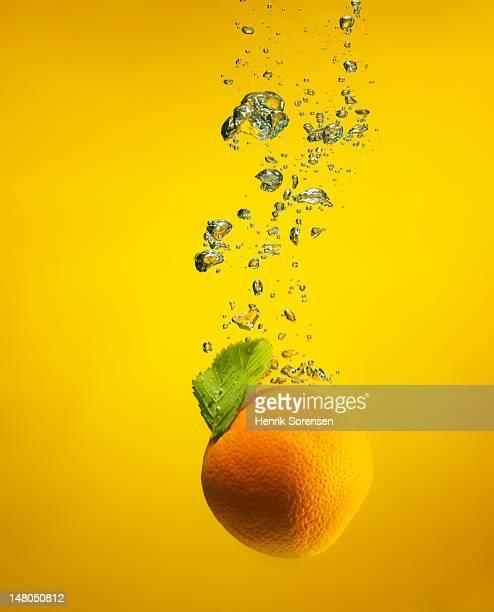 An orange splashed into water