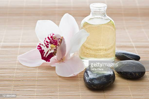 An orchid, aromatherapy oil and Lastone therapy stones on a Tatami mat