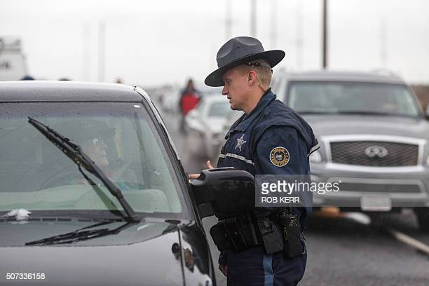 An Oregon State Police officer talks with a person at a road checkpoint on Highway 78 approximately 4 miles from the Malheur Wildlife Refuge...