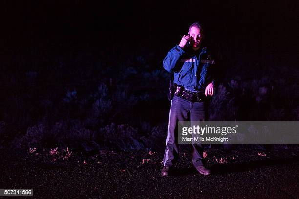 An Oregon State Trooper speaks on the phone at a road block during the evening near Malheur National Wildlife Refuge January 28 2016 near Burns...