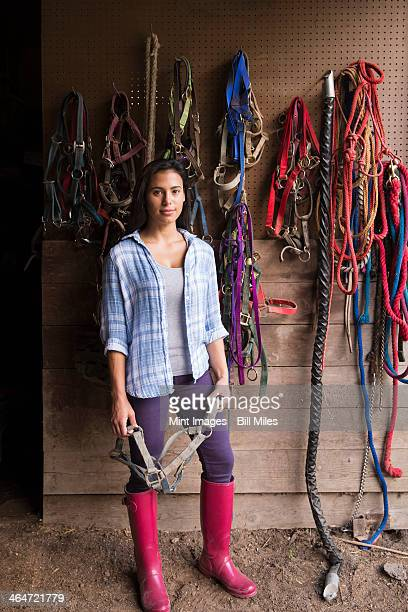 An organic farm in the Catskills. A person standing in a tack room in a stable.