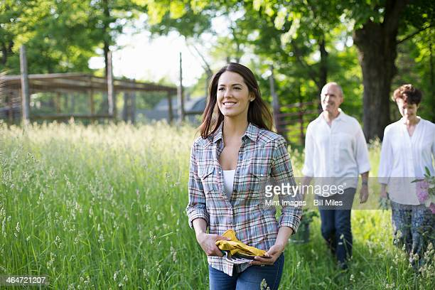 An organic farm in the countryside near Woodstock. Summer party. Two mature people, a couple and a young woman walking through the long grass.