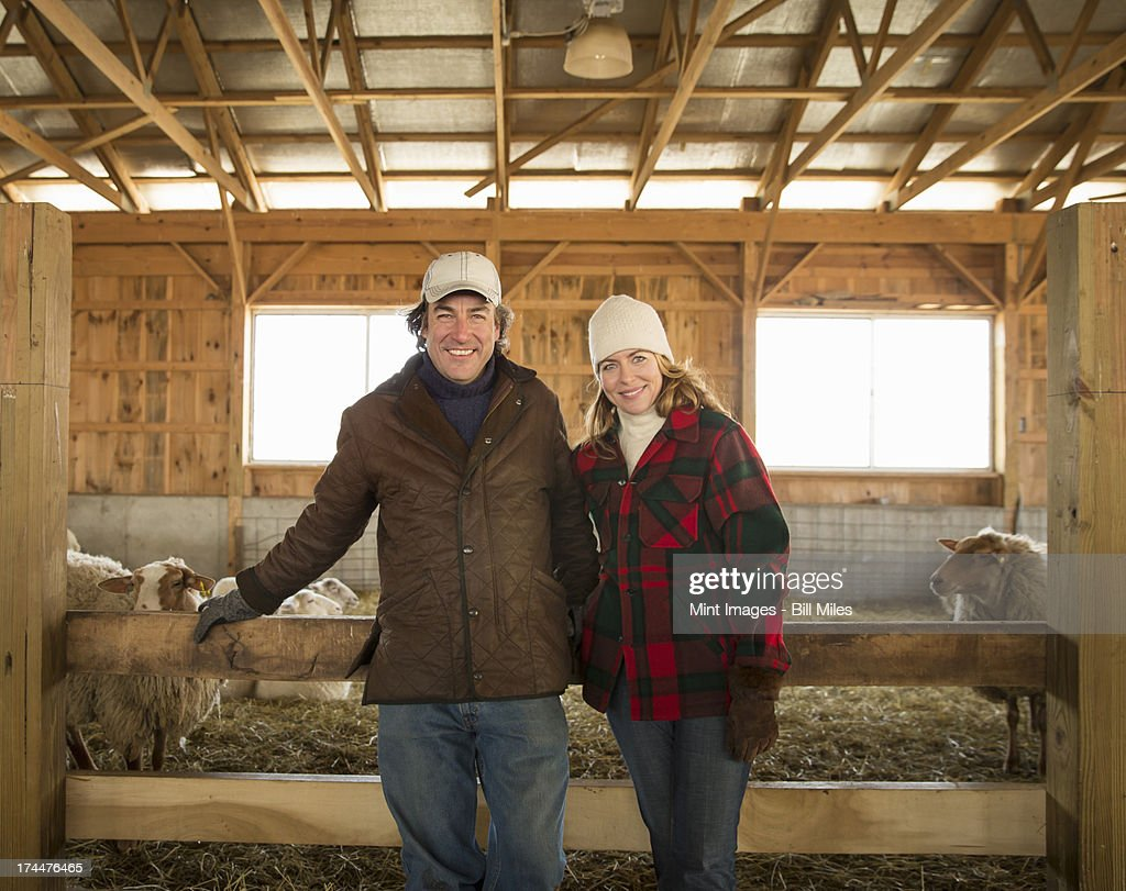 An Organic Farm in Winter in Cold Spring, New York State. A farmer and a woman standing by a pen full of sheep. : Stock Photo
