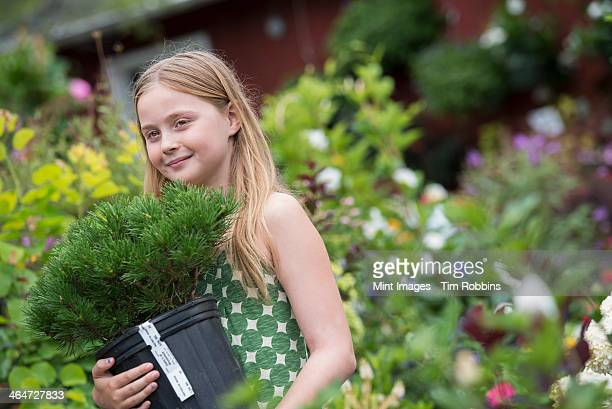 An organic flower plant nursery. A young girl carrying a plant in a pot.