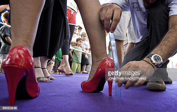An organiser measures the length of an Israeli woman's heel prior to the 'Race on Heels' near the beach in Tel Aviv on July 16 2009 The competition...