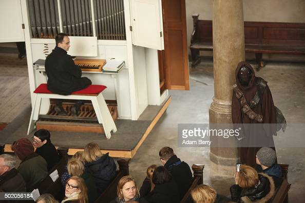 An organist looks at a man dressed as a Star Wars Jawa character during a church service centered around the 1983 film 'Star Wars Episode VI Return...