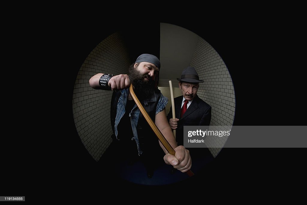 An organized crime boss and his bodyguard, viewed through a peephole