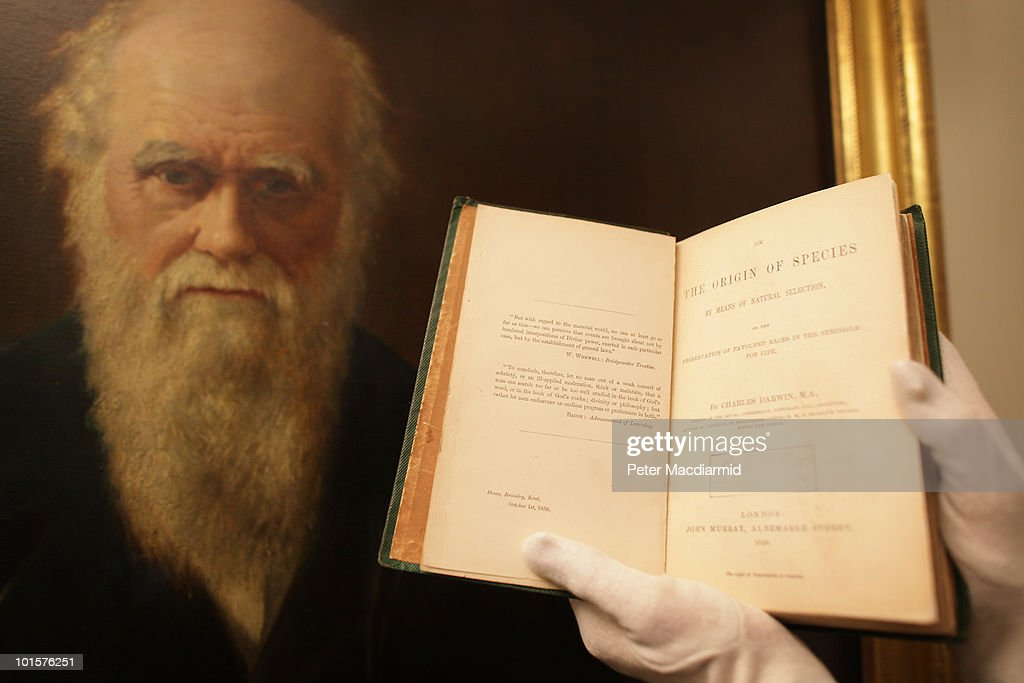 An original copy of The Origin of Species which forms part of 'The Royal Society350 Years of Science' exhibition is displayed in front of a portrait...