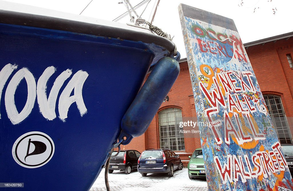 An original piece of the Berlin Wall with graffiti of the words 'Next Wall to Fall Wall Street' stands outside a meeting of the Berlin chapter of the German Pirate Party near a boat featuring a sticker of the party's logo on February 23, 2013 in Berlin, Germany. After successes in 2011 in regional elections in the German capital and in the following year in the states of Schleswig-Holstein and North Rhine-Westphalia, the German Pirate Party (Piratenpartei), which initially focused on filesharing, censorship and data protection, has seen two of its state-level leaders in the states of Brandenburg and Baden-Wuerttemburg step down in the past few days alone. The party's Berlin representation is meeting over the weekend to choose its candidates for the country's federal elections, to be held on September 22, 2013, which will determine the 598 or more members of the 18th Bundestag, Germany's federal parliament. After well-publicized infighting in the party, many observers are skeptical that the party can reach the 5 percent vote required to join the country's politics on that level.