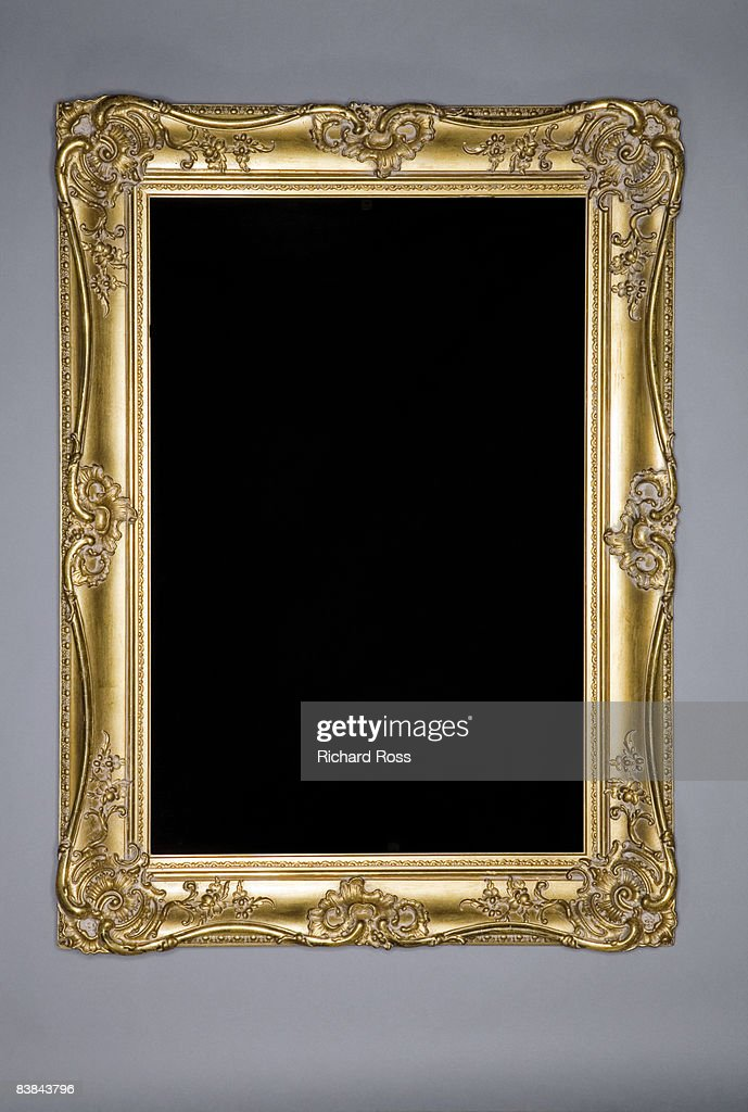 An ornate gold frame on a grey-blue wall