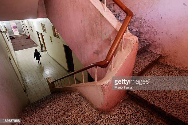 An orphan walks through a hallway of an orphanage on December 12 2011 in Baghdad Iraq Estimates suggest there may be more than one million orphans...