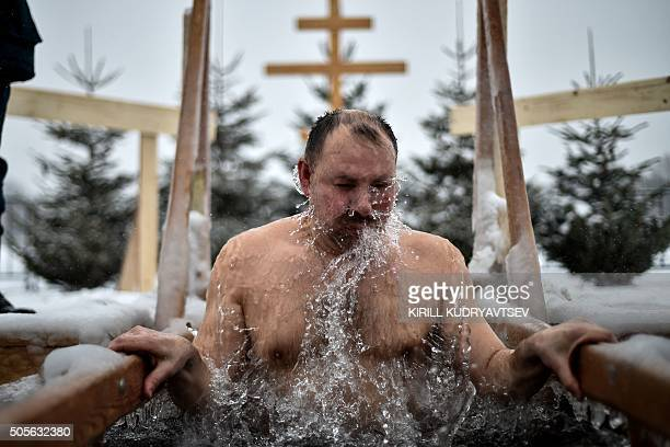 An Orthodox believer dips into the icy waters of a pond on January 19 2016 during the celebration of the Epiphany holiday in Moscow Among Orthodox...