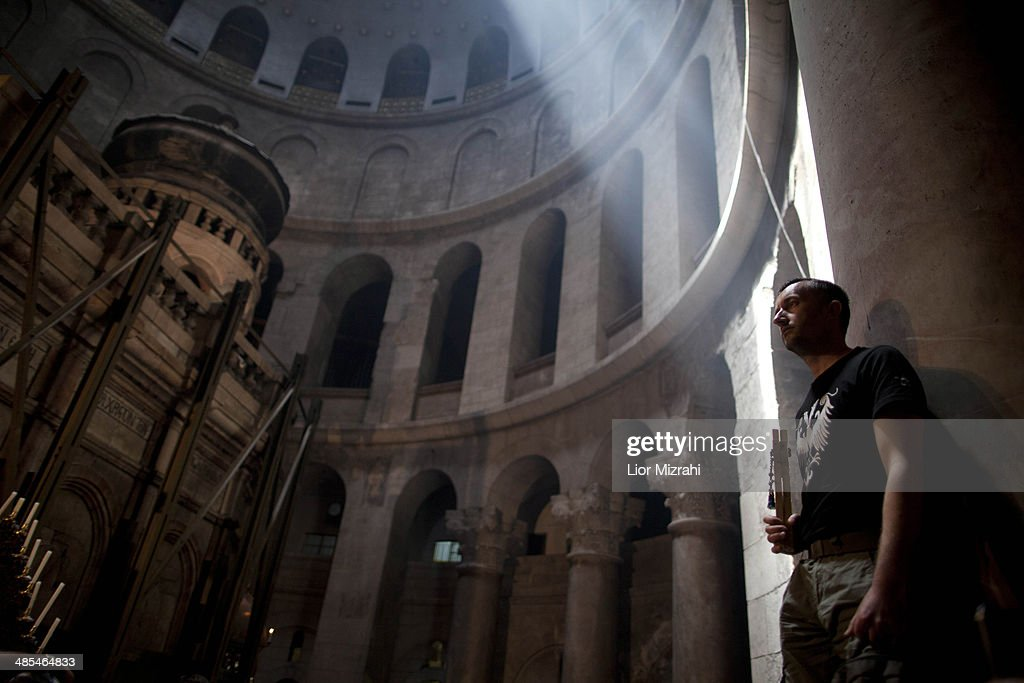 An Orthodox Christian pilgrim holds a wooden cross as he stands in the Church of the Holy Sepulchre on April 18, 2014 in Jerusalem's old city, Israel.Thousands of Christian pilgrims from around the world have flocked to the Holy City to mark Good Friday and pray along the traditional route Jesus Christ took to his crucifixion, leading up to his resurrection on Easter.