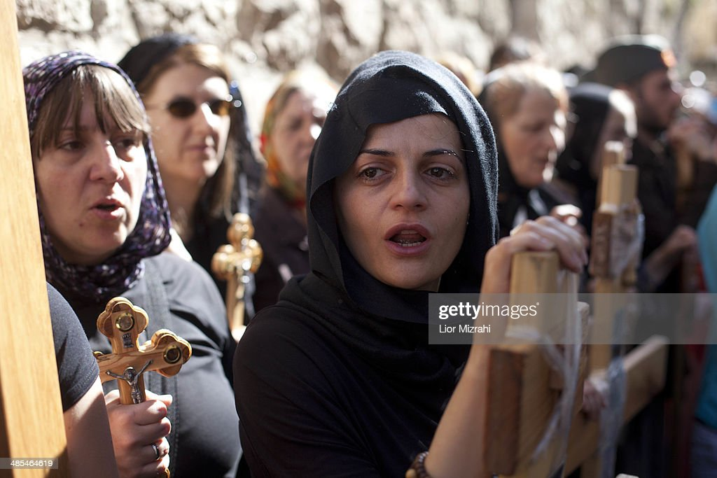 An Orthodox Christian pilgrim holds a wooden cross as she takes part in the Good Friday procession along the Via Dolorosa on April 18, 2014 in Jerusalem's old city, Israel.Thousands of Christian pilgrims from around the world have flocked to the Holy City to mark Good Friday and pray along the traditional route Jesus Christ took to his crucifixion, leading up to his resurrection on Easter.
