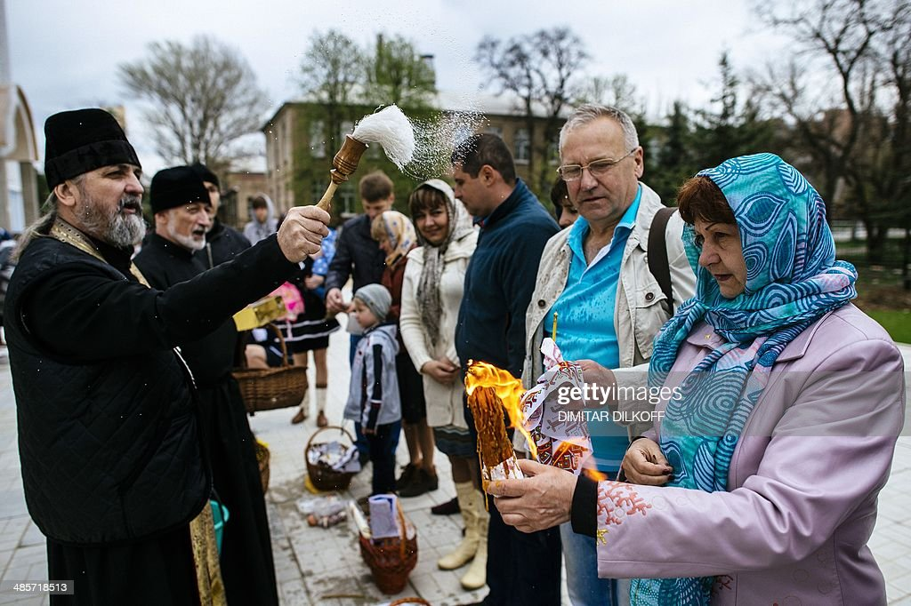An Orthodox Christian priest blesses a woman holding a candle as they take part in Easter celebrations outside a church in the eastern Ukrainian city of Lugansk on April 20, 2014.