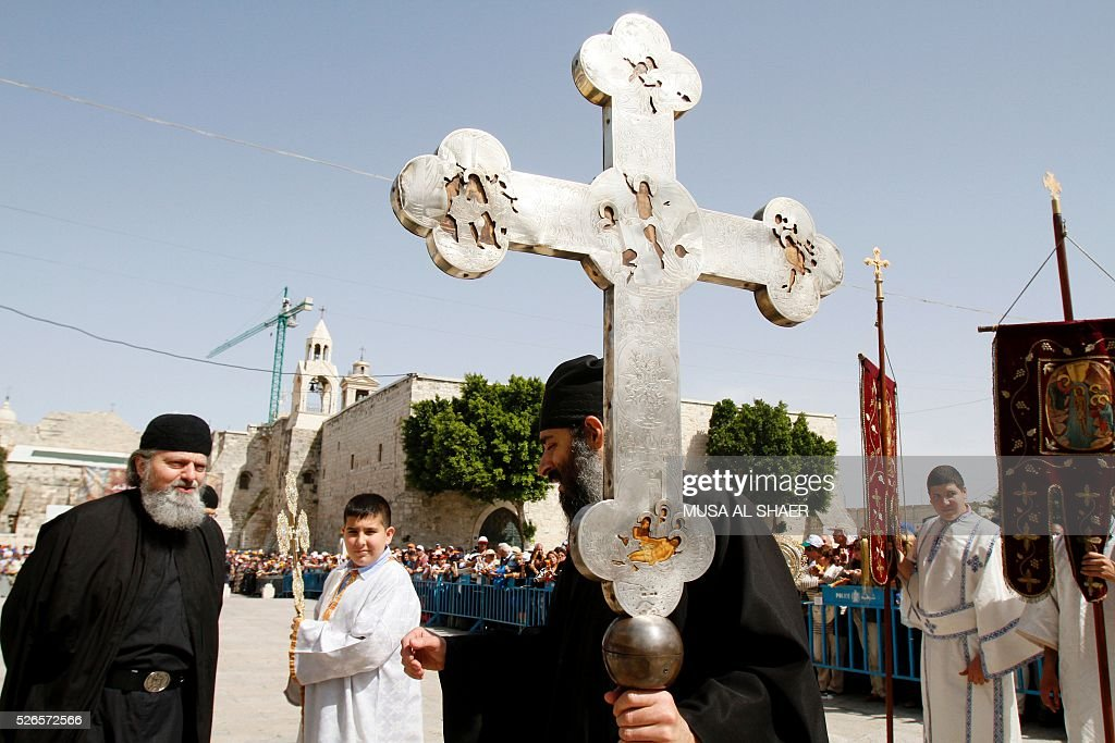 An Orthodox Christian priest holds a cross outside the Church of the Nativity in the biblical west bank town of Bethlehem on April 30, 2016, during the Orthodox Easter ceremony of the 'Holy Fire'. The ceremony is marked by the appearance of 'sacred fire' in the two cavities on either side of the Holy Sepulchre, in the Church of the Sepulchre in Jerusalem, and Christians all over the world light candles representing this 'Holy Fire'. The Holy Sepulchre in Jerusalem is the site of the tomb of Jesus Christ according to Christian tradition. / AFP / MUSA