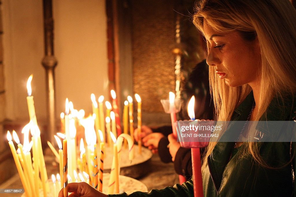 An Orthodox Christian woman lights candles as she celebrates Orthodox Easter during a midnight mass at the main church in Korca, Albania, early on April 20, 2014.