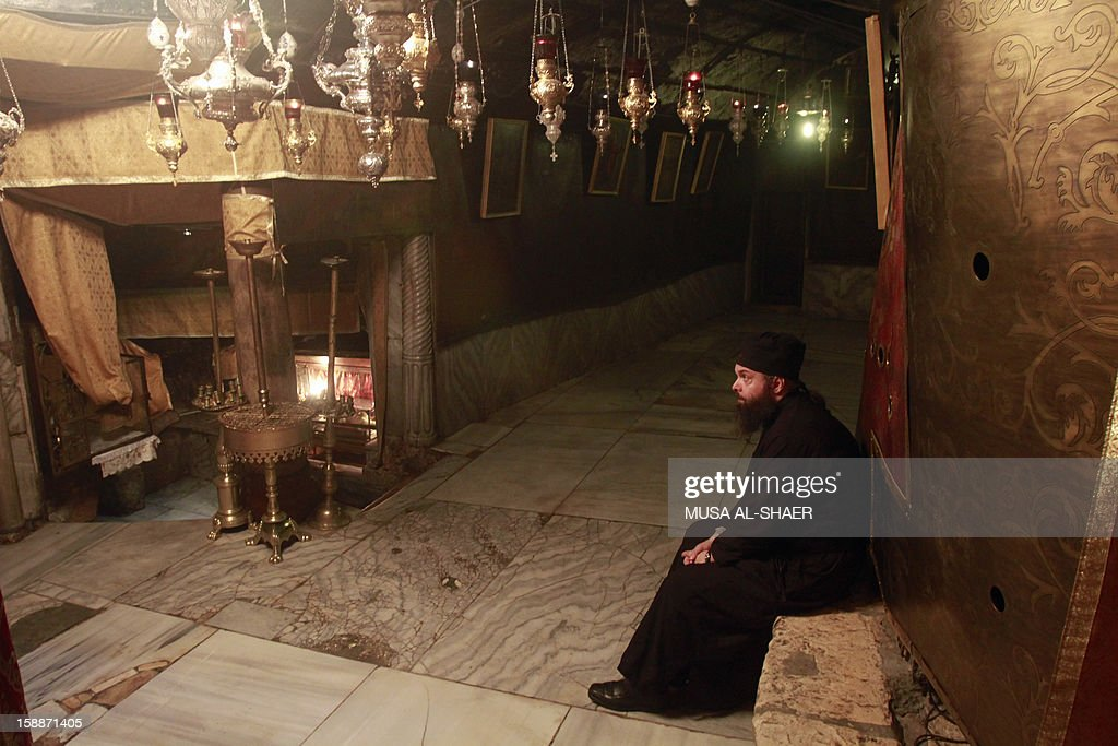 An Orthodox clergyman rests during the cleaning of the the Church of Nativity following Christmas festivities on January 2, 2013, in the West Bank town of Bethlehem. The sovereignty of the Church of the Nativity, traditionally believed to be the birthplace of Jesus Christ, is shared by the Christian denominations, who also share the annual cleaning responsibilities.