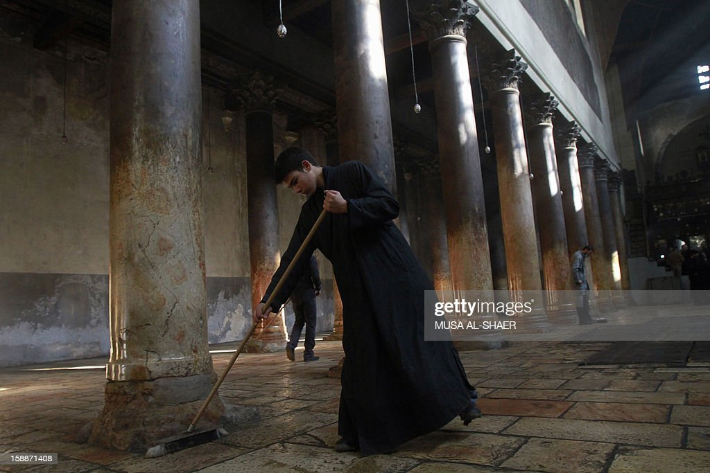 An Orthodox clergyman sweeps inside the Church of Nativity following Christmas festivities on January 2, 2013 in the West Bank town of Bethlehem. The sovereignty of the Church of the Nativity, traditionally believed to be the birthplace of Jesus Christ, is shared by the Christian denominations, who also share the annual cleaning responsibilities.