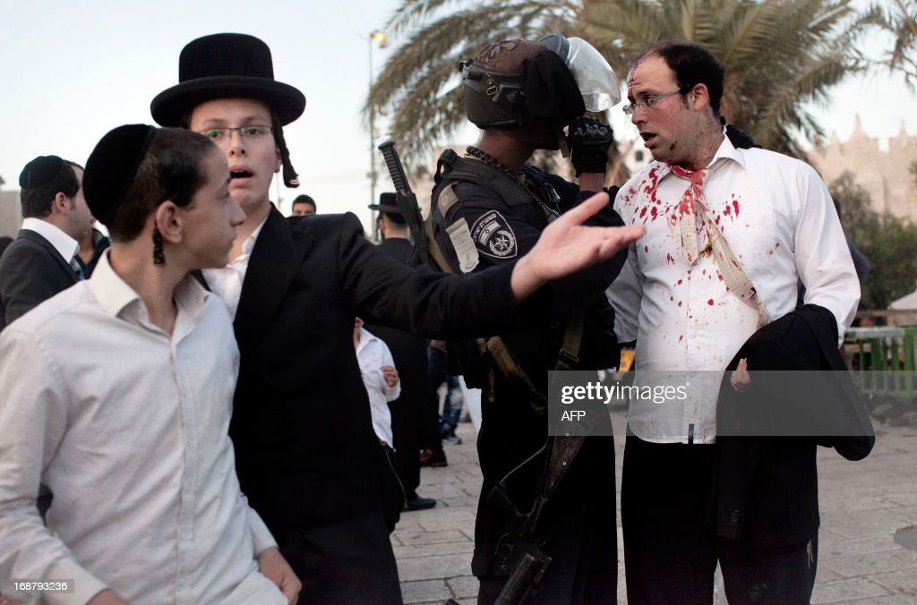 An Orthodox Jew, bleeding after he was hit in the head by a stone, is escorted by an Israeli policeman outside Jerusalem's Damascus Gate to receive medical attention on May 15, 2013. The man was injured during clashes that followed a rally by Palestinian protestors to mark the 65th Nakba or 'catastrophe' of the Jewish state's creation in 1948, during which 760,000 Palestinians fled their homes.