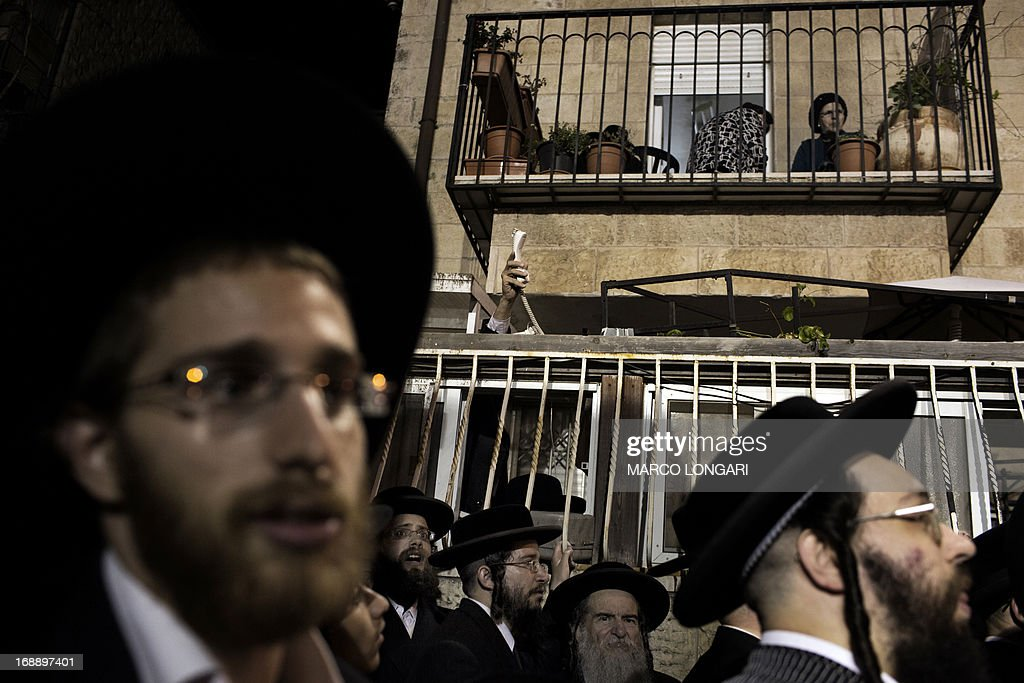 An Orthodox Jew raises a telephone to transmit the speech of a religious leader while gathering with thousands other Orthodox Jews in front of the main army recruitment office in Jerusalem on May 16, 2013 to demonstrate against any plans to make them undergo military service, a police spokesman said. Protesters also prayed and chanted 'the Torah above everything!' referring to Jewish religious law, and 'the army will not take yeshiva (religious seminary) pupils.'