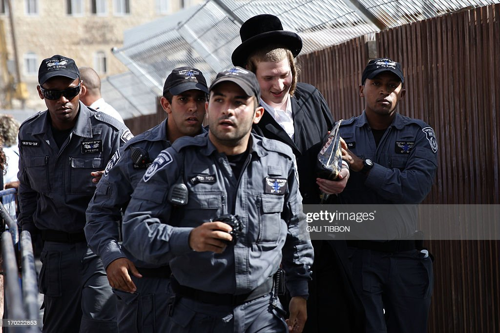 An Orthodox Jewish man is arrested by Israeli policemen as he protested against members of the liberal Jewish religious group Women of the Wall who pray with traditional Jewish prayer apparel for men on June 9, 2013 at the Western Wall in Jerusalem's Old City marking the first day of the Jewish month of Tamuz.