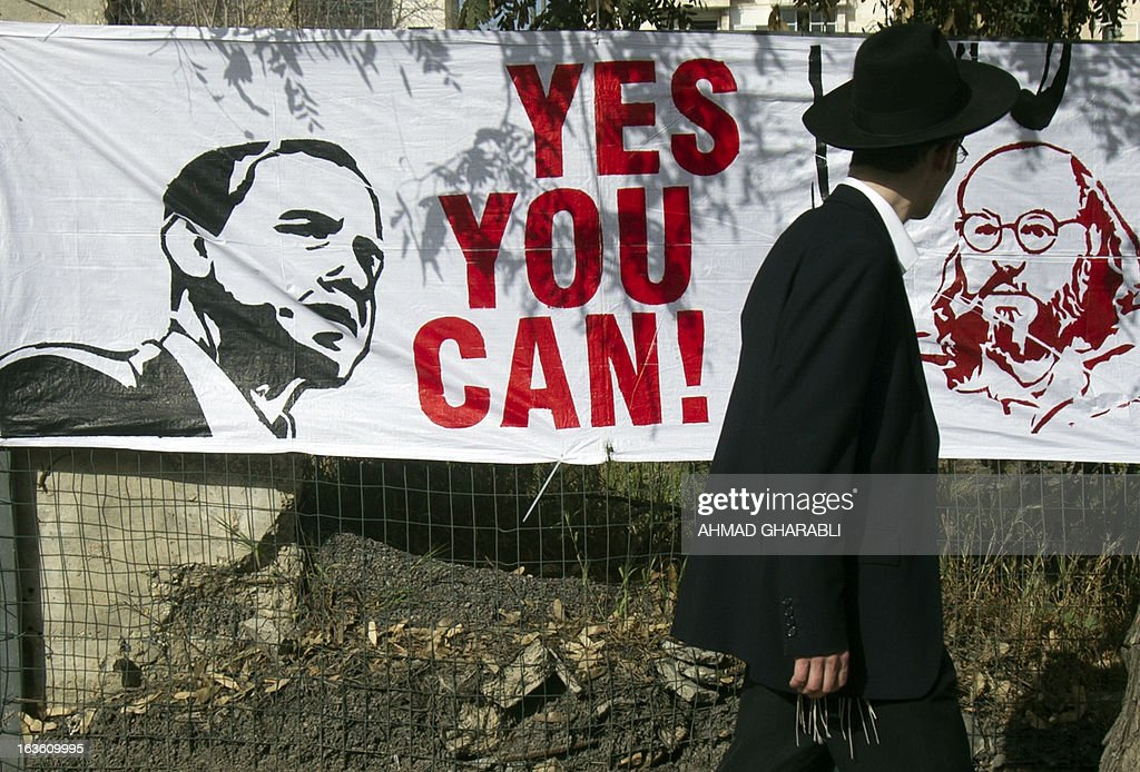 An Orthodox Jewish man walks past a banner on March 13, 2013, in Jerusalem, calling on US President Barack Obama to free Jonathan Pollard, an American who was convicted of spying for Israel and who is serving a life sentence since 1987 in the United State. Jerusalem and other cities in Israel and in the Palestinian West Bank are preparing for the upcoming visit of US President Obama's three-day visit which will begin on March 20.