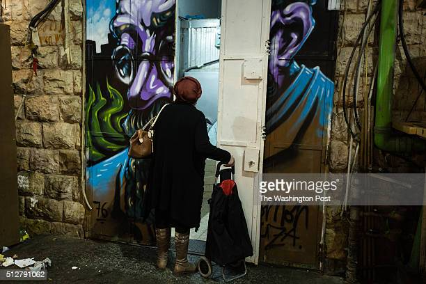 An orthodox Jewish woman stands in front of a graffiti depicting an unrecognized Jewish personality which was painted over a shutter as she does some...