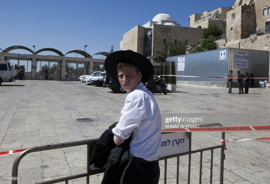 An Orthodox Jewish youth watches as Israeli security forces inspect the area around the Wailing Wall, the holiest site where Jews can pray, in Jerusalem's Old City on June 21, 2013 after an Israeli security guard shot dead a Jewish visitor apparently mistaking him for a Palestinian militant. The shooting took place shortly before 8 am (0500 GMT) as the plaza in front of the Wall filled with worshippers for morning prayers ahead of the start of the Jewish Sabbath at sundown. AFP PHOTO / AHMAD GHARABLI