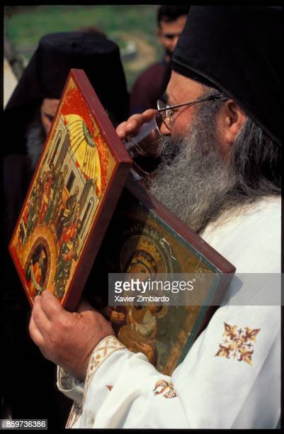 An Orthodox monk carrying icons and drinking a glass of red holy wine at Easter on April 27 1997 in the Mount Athos Monastic Republic Greece