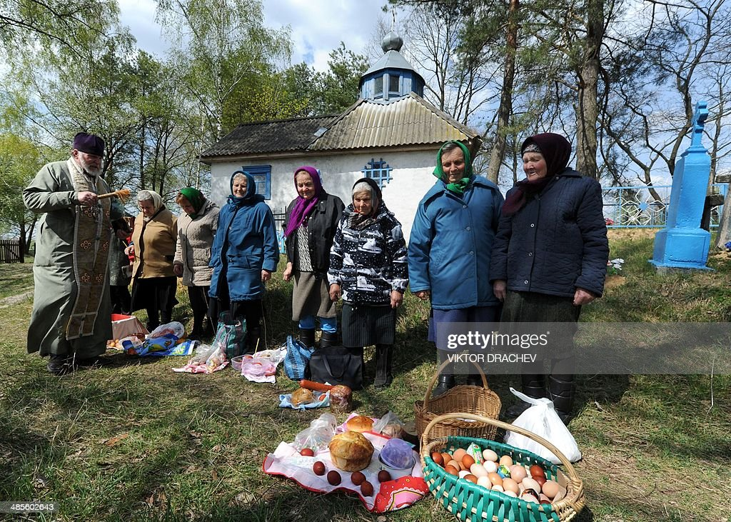 An Orthodox priest blesses cakes and colored eggs during an Orthodox Easter ceremony in the village of Semurovtsy, some 260km south of Minsk, on April 19, 2014, on the eve of the Orthodox Easter.
