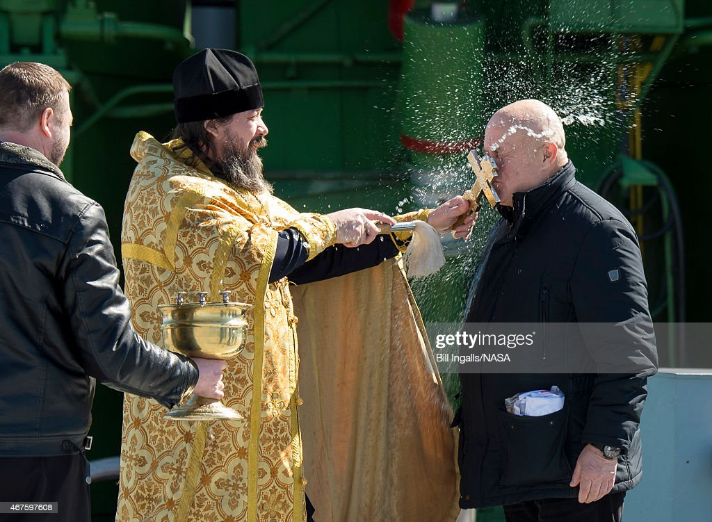 An Orthodox Priest blesses Sergey Semchenko of the Russian Search and Recovery Forces after having blessed the Soyuz rocket at the Baikonur Cosmodrome Launch pad March 26, 2015 at the Baikonur Cosmodrome in Kazakhstan. NASA Astronaut Scott Kelly, and Russian Cosmonauts Mikhail Kornienko, and Gennady Padalka of the Russian Federal Space Agency are scheduled to launch to the International Space Station in the Soyuz TMA-16M spacecraft from the Baikonur Cosmodrome on March 28 (March 27 EST) returning to Earth on Soyuz TMA-18M in March 2016.