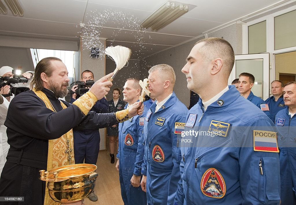 An Orthodox priest blesses the International Space Station (ISS) crew members, (L to R) US astronaut Kevin Ford and Russian cosmonauts Oleg Novitskiy and Evgeny Tarelkin before they leave for a final pre-launch preparation at the Baikonur cosmodrome October 23, 2012. AFP PHOTO / POOL / Sergei Remezov