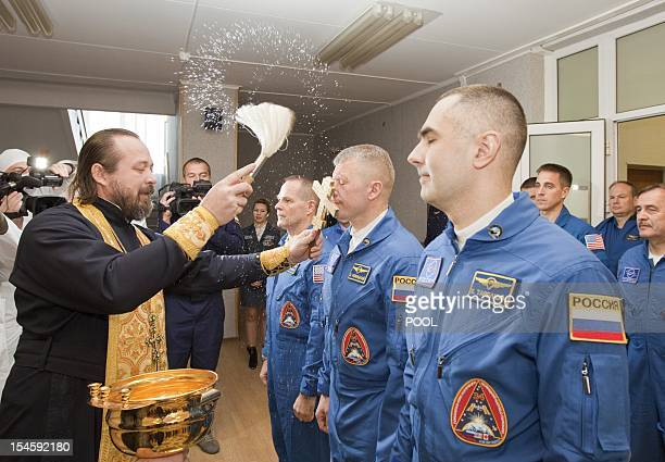An Orthodox priest blesses the International Space Station crew members US astronaut Kevin Ford and Russian cosmonauts Oleg Novitskiy and Evgeny...