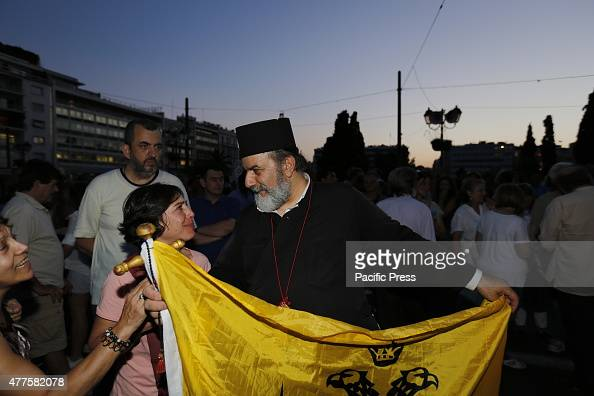 SQUARE ATHENS ATTICA GREECE An orthodox priest carrying a flag of the Greek Orthodox Church takes part in the progovernment protest Greeks assembled...