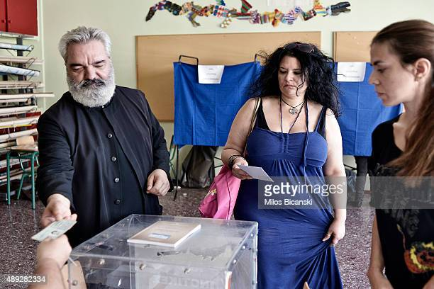 An Orthodox priest gets ready to cast his ballot at a polling station on September 20 2015 in Athens Greece The latest polls have the incumbent...