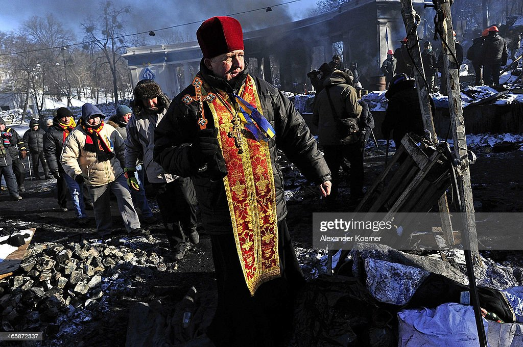 An Orthodox priest holds a crucifix at a barricade at Grushevskogo Street on January 30, 2014 in Kiev, Ukraine. Ukraine's Prime Minister Mykola Azarov and his cabinet resigned two-days ago following months of protests, while parliament is also scrapping a number of controversial anti-protest laws. Radical anti-government protesters have started to build new walls inside the existing barricades in defiance of the Government's proposed Amnesty.